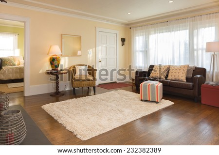 Large beige living room with rug, leather couch, recessed lighting, and fireplace adjacent to library and dining room. - stock photo