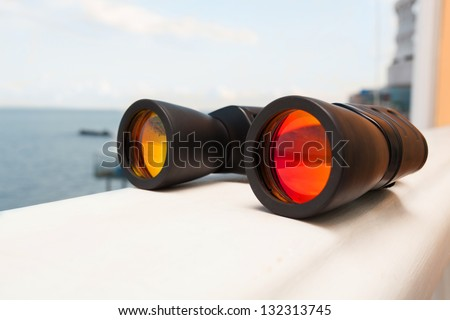 large binoculars on railing against the sea