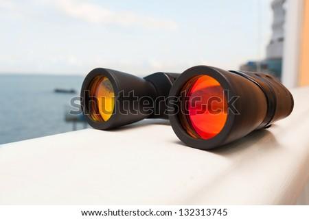 large binoculars on railing against the sea - stock photo