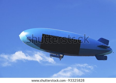 Large blimp with black digital screen on a blue background with white clouds - stock photo