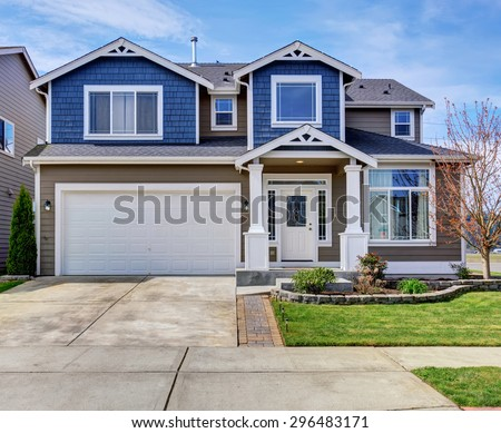 Large blue and gray home with white trim, also a driveway.
