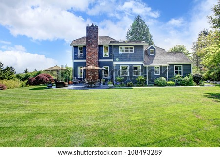 Large blue house exterior with grass and chimney. - stock photo
