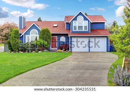 Large blue house with white trim, and well kept lawn, along with two garage spaces. - stock photo