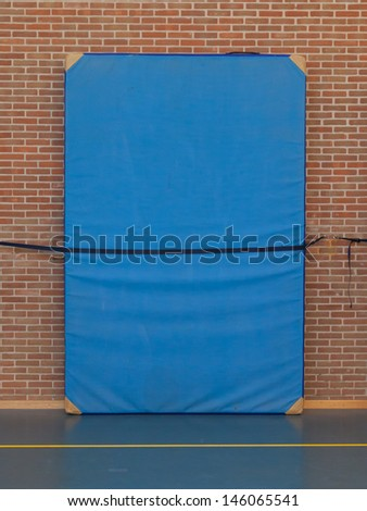 Large blue mat strapped to a brick wall, gym - stock photo