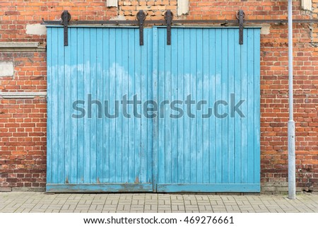 Large, blue wooden door in a brick house / blue wooden gate / Architecture Detail