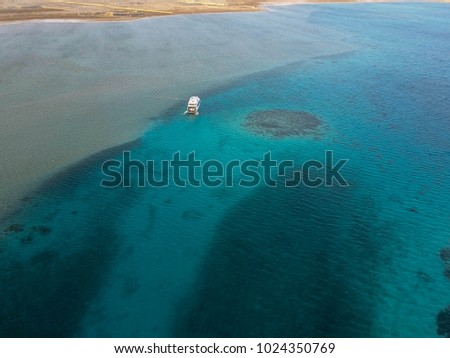 LARGE BOAT CRUISING THROUGH THE SALLOW AMAZING WATERS OF THE RED SEA IN EGYPT