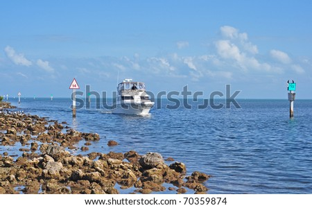 Large Boat entering a dock using a chanel showing navigational signs, in South Florida - stock photo