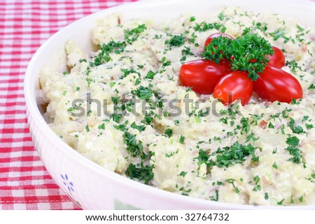 Large bowl of homemade potato salad with grape tomatoes.  Garnished with fresh parsley. - stock photo