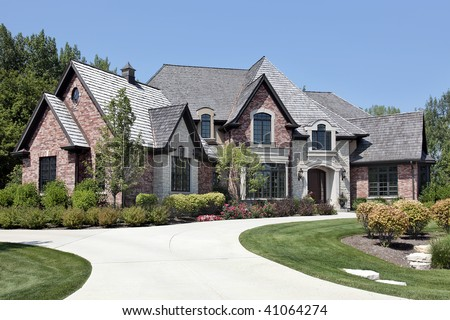 Large brick home in suburbs with circular driveway - stock photo