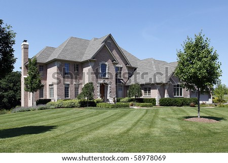 Large brick home with stone arched entry - stock photo