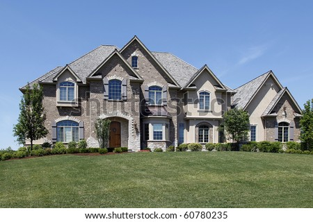 Large brick home with stone entry and wooden door - stock photo