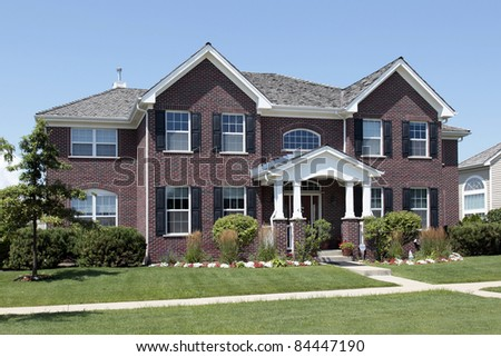 Large brick home with white arched entry - stock photo