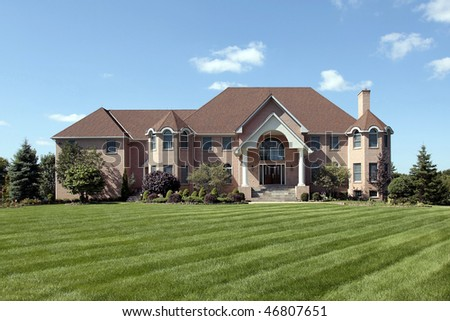 Large brick luxury home with arched entry - stock photo