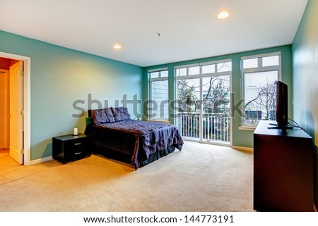 Large bright blue bedroom with purple bed and balcony door.