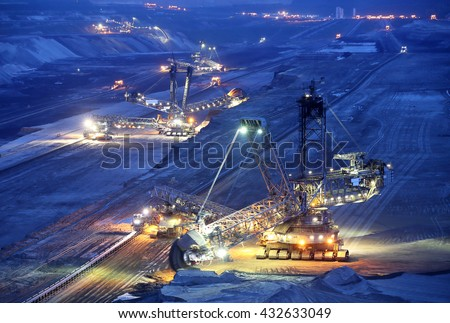 Large bucket wheel excavators in a lignite (brown-coal) mine after sunset, Germany - stock photo