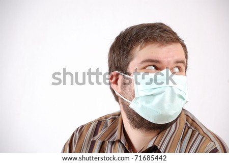 large-built mid-adult man wearing a surgical face mask - stock photo