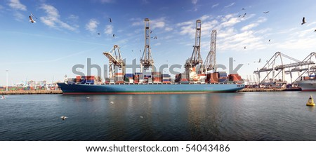 Large bulk carrier moored off at the Rotterdam Harbor, being unloaded of its containers by large cranes - stock photo