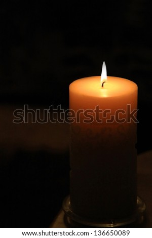 Large candle with flame - candlelight, lit in darkness, religious icon, peace, hope or Christmas or Christian / religious symbol.  - stock photo