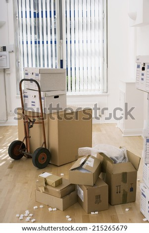 Large cardboard box on hand truck in office, small boxes on wooden floor near packing foam - stock photo