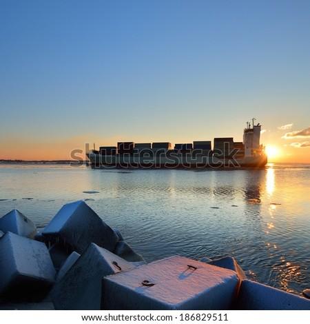 Large cargo container ship sailing against the sunset . Riga, Latvia - stock photo