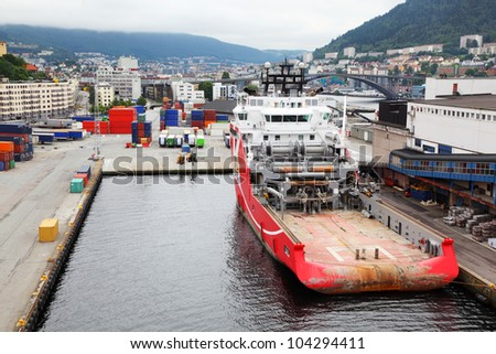 Large cargo ship are in dock in coastal city, many containers stand around - stock photo