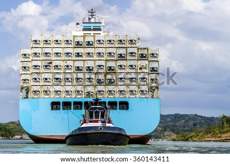 Large cargo ship being guided and towed through the Panama Canal carrying large freights. - stock photo