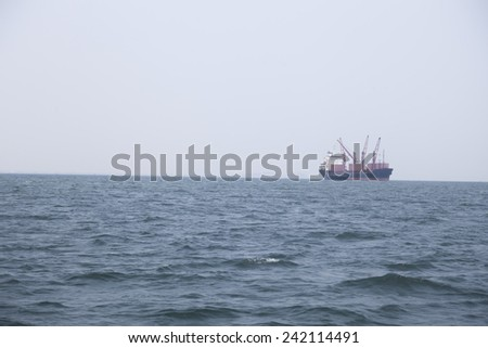 Large cargo ship Boats moored in the sea to make sense compared to the coast.