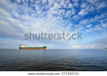 Large cargo ship (Bulk carrier) sailing in a bright sunny day.  - stock photo