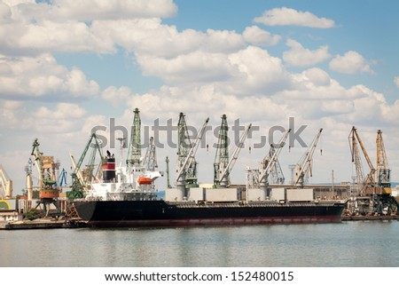 Large cargo ship in a dock at port. Cloudy sky