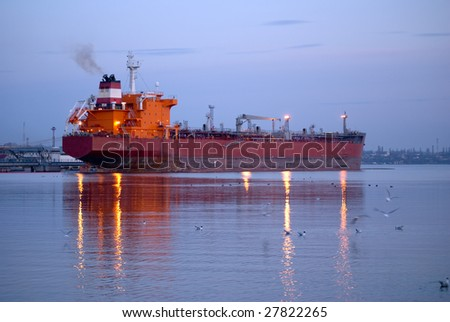 Large cargo ship in a harbor. Twilight. Lights reflections of the water.
