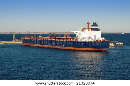 Large cargo ship is being fueled in a harbor