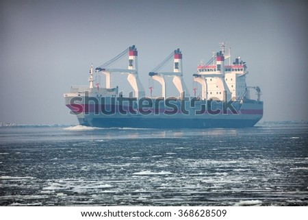 large cargo ship sailing in winter waters with ice