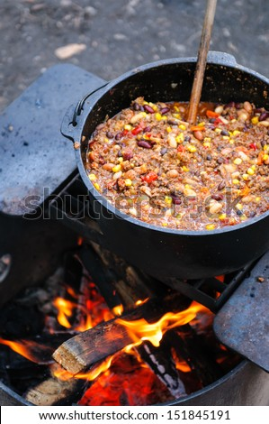 Large cast iron pot of spicy chili cooking over a campfire - stock photo