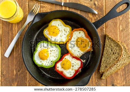 Large cast iron skillet with fried eggs in green, yellow, red and orange bell peppers sitting on wooden table with glass of orange juice and whole wheat toast - stock photo