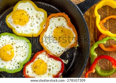 Large cast iron skillet with fried eggs in green, yellow, red and orange bell peppers sitting on wooden table with pepper slices - stock photo
