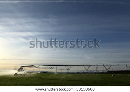 Large center pivot irrigation system operating in the late afternoon in Canterbury New Zealand - stock photo