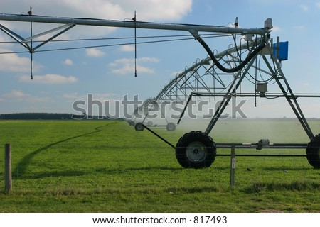 Large center pivot irrigation system running on an open plains dairy farm in Canterbury, New Zealand.