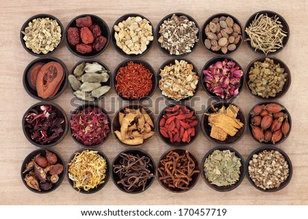 Large chinese herbal medicine selection in wooden bowls over papyrus background. - stock photo