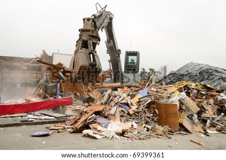 Large clamshell bucketed track hoe tearing down a former restaurant for a new commercial building project in Roseburg OR - stock photo