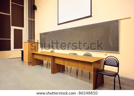 Large classroom, big blackboard, wooden table and black chairs - stock photo