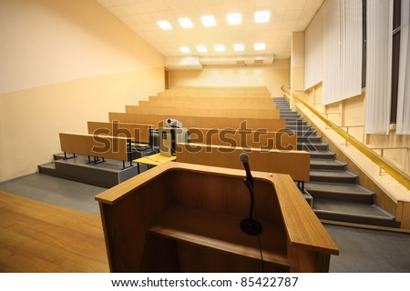 Large classroom, university lecture hall; view from lectern with microphone - stock photo