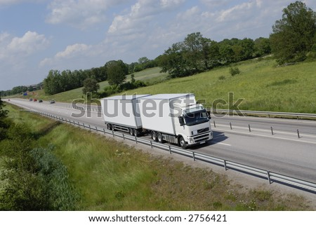 large clean truck driving on highway surrounded by spring-green countryside - stock photo