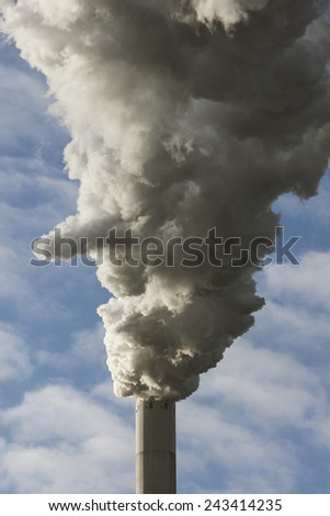 Large cloud of smoke from coal fired power plant against blue clouded sky - stock photo