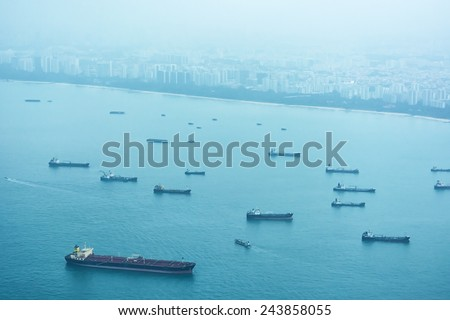 Large collection of commercial cargo ships waiting at the anchorage just off the coast of Singapore. - stock photo