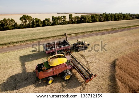 Large combine unloading seed into a grain cart on a prairie field - stock photo