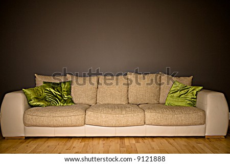 Large comfortable couch against a dark grey background - stock photo