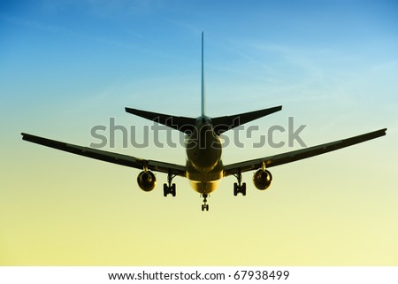 Large commercial airplane flying overhead landing with the sunset light in the background
