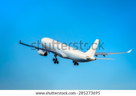 Large commercial passenger airplane taking off into the blue sky - stock photo