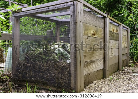 Large compost bin, made of wood and wire mesh, in a community garden, early summer in Illinois, for themes of environment, recycling, organic fertilization