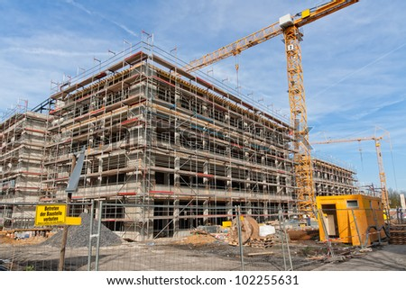 Large construction site with scaffolding building, yellow tower crane and clear blue sky. - stock photo